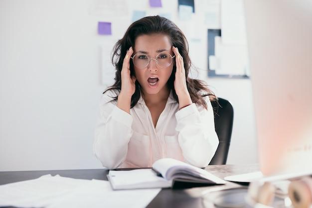 Vista frontal de uma jovem profissional com óculos redondos e blusa branca, sentada ao lado da mesa com impressão estressada no rosto, boca aberta