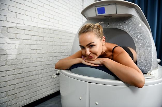 Vista frontal de uma jovem relaxando enquanto recebia um tratamento de cápsula de spa de bem-estar em uma clínica de spa moderna. fechar-se