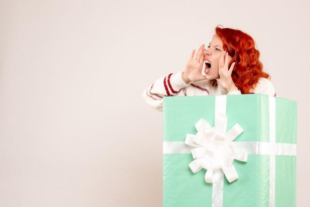 Vista frontal de uma jovem se escondendo dentro de um presente gritando na parede branca