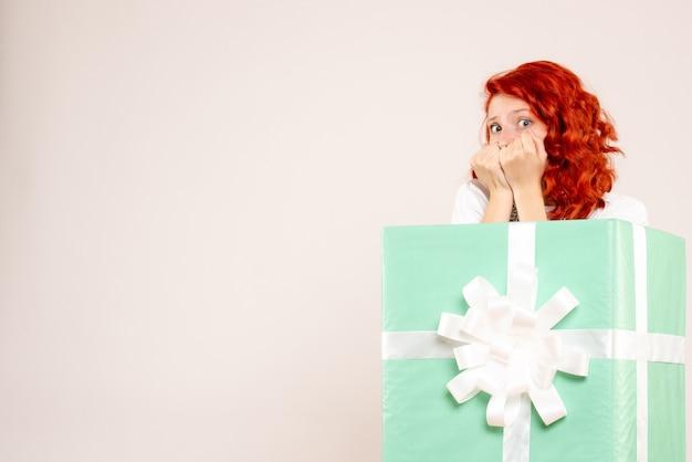Vista frontal de uma jovem se escondendo dentro de uma parede branca