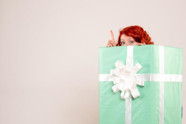 Vista frontal de uma jovem se escondendo dentro do presente de natal na parede branca