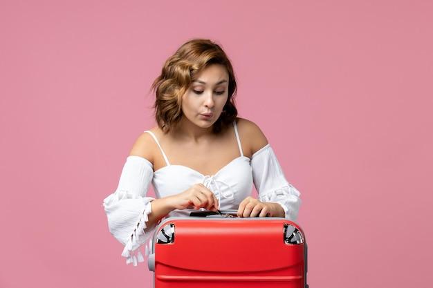Vista frontal de uma jovem se preparando para as férias com a bolsa na parede rosa