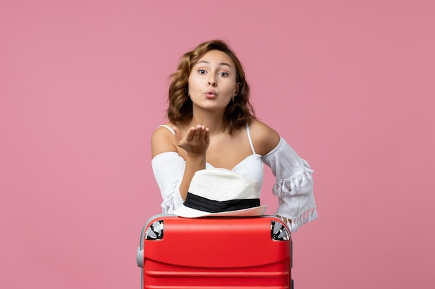 Vista frontal de uma jovem se preparando para as férias enviando beijos no ar na parede rosa