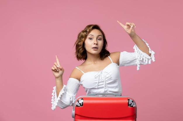 Vista frontal de uma jovem se preparando para uma viagem de verão com uma bolsa vermelha na parede rosa