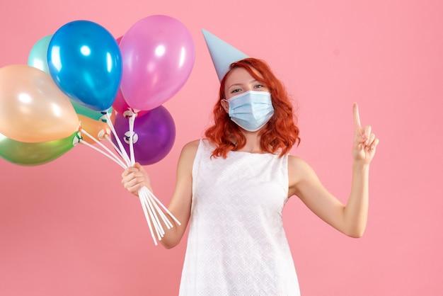 Vista frontal de uma jovem segurando balões coloridos em uma máscara estéril na parede rosa