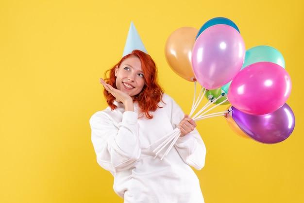 Vista frontal de uma jovem segurando balões coloridos na parede amarela
