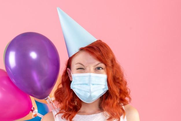 Vista frontal de uma jovem segurando balões coloridos na parede rosa