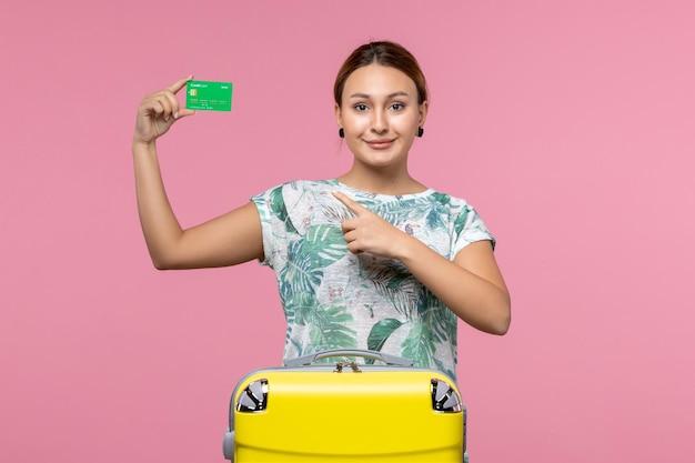 Vista frontal de uma jovem segurando o cartão do banco e sorrindo na parede rosa