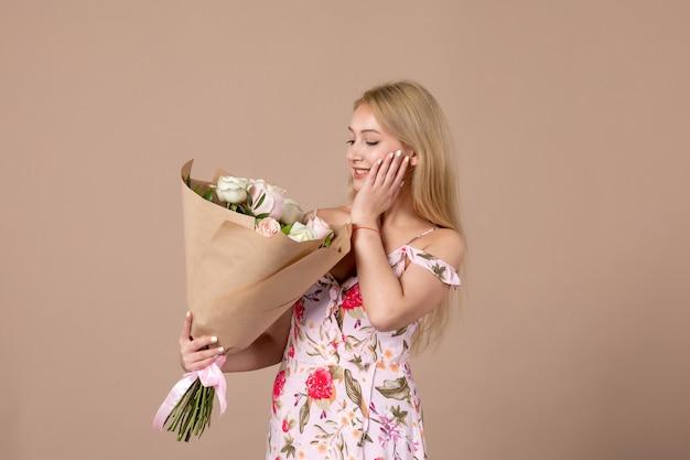 Vista frontal de uma jovem segurando um buquê de lindas rosas na parede marrom