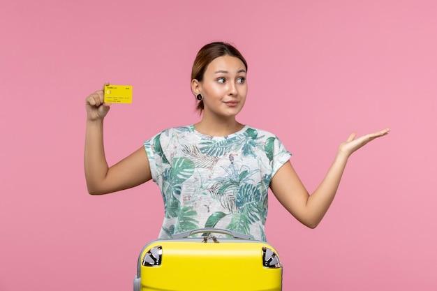 Vista frontal de uma jovem segurando um cartão amarelo na parede rosa