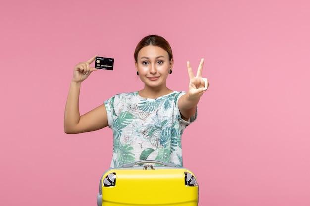 Vista frontal de uma jovem segurando um cartão do banco com um sorriso na parede rosa