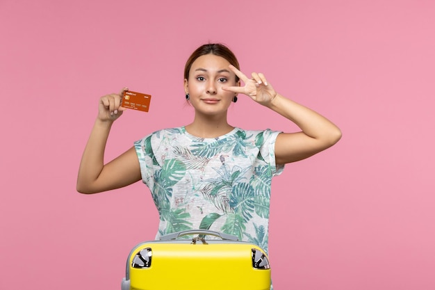 Vista frontal de uma jovem segurando um cartão do banco marrom e posando na parede rosa