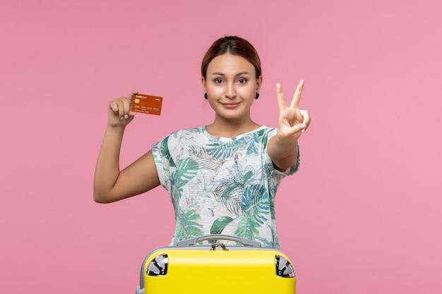 Vista frontal de uma jovem segurando um cartão do banco marrom e sorrindo na parede rosa