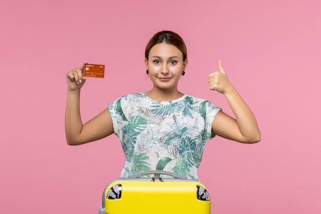 Vista frontal de uma jovem segurando um cartão do banco marrom na parede rosa claro