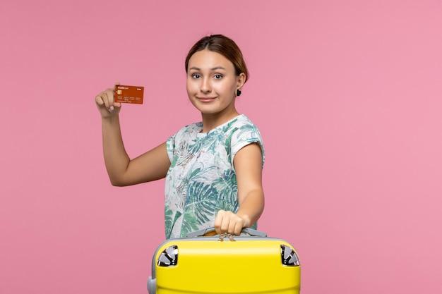 Vista frontal de uma jovem segurando um cartão do banco marrom na parede rosa