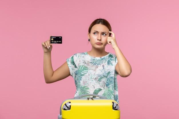 Vista frontal de uma jovem segurando um cartão preto do banco na parede rosa
