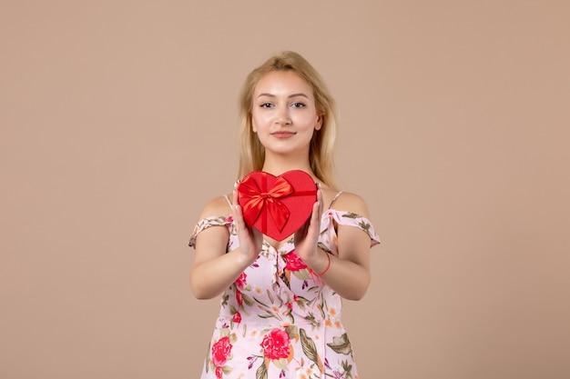 Vista frontal de uma jovem segurando um coração vermelho em forma de presente na parede marrom