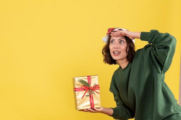 Vista frontal de uma jovem segurando um pequeno presente de natal na parede amarela