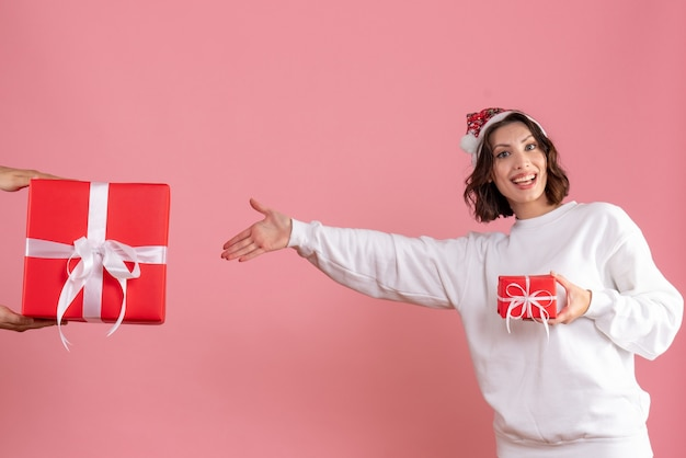 Vista frontal de uma jovem segurando um presentinho e não aceitando o presente do homem na parede rosa