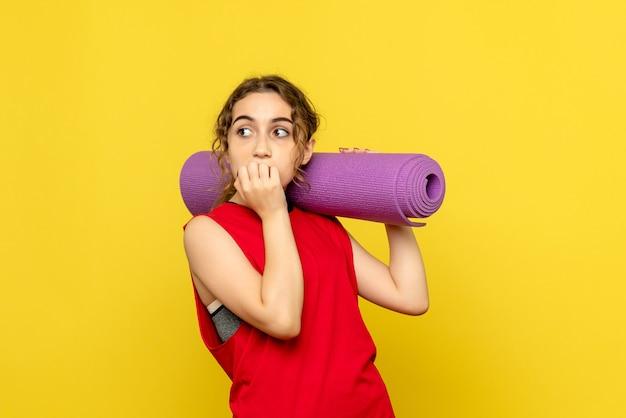 Vista frontal de uma jovem segurando um tapete roxo na parede amarela