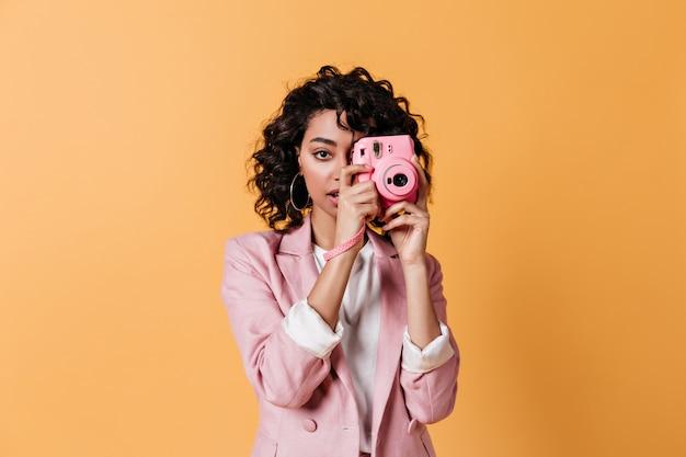 Vista frontal de uma jovem segurando uma câmera rosa