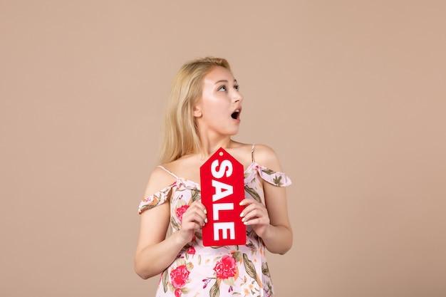 Vista frontal de uma jovem segurando uma placa vermelha de venda na parede marrom
