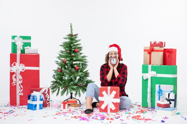 Vista frontal de uma jovem sentada ao redor de presentes de natal segurando relógios na parede branca