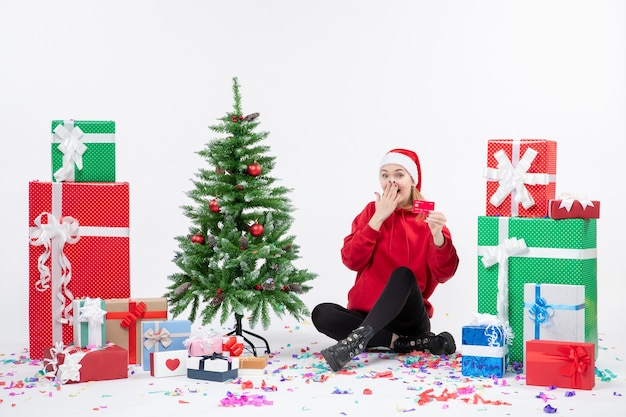 Vista frontal de uma jovem sentada com presentes segurando um cartão vermelho do banco na parede branca