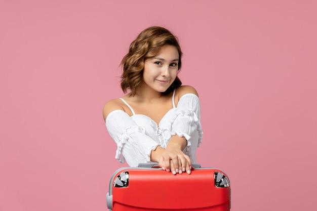 Vista frontal de uma jovem sorrindo com uma bolsa vermelha na parede rosa