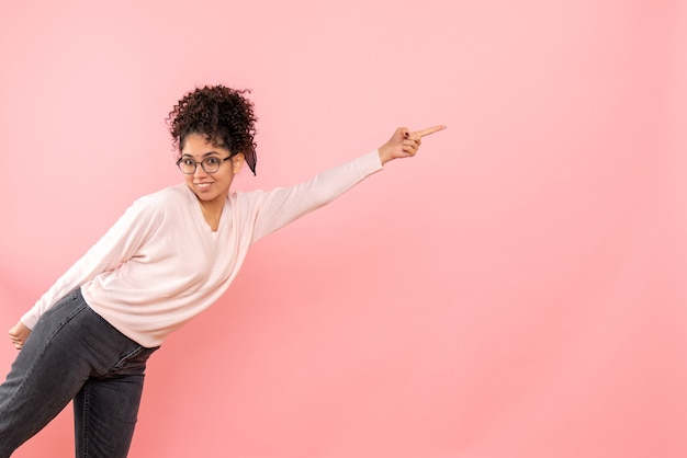 Vista frontal de uma jovem sorrindo na parede rosa