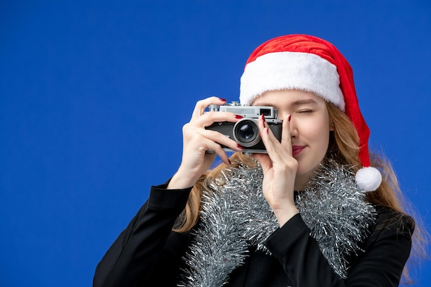 Vista frontal de uma jovem tirando foto com a câmera na parede azul