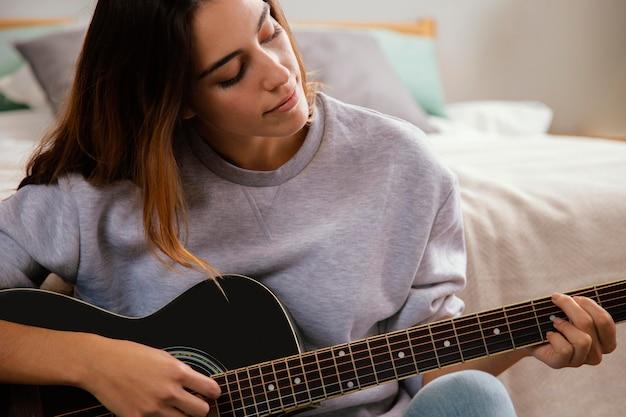 Vista frontal de uma jovem tocando violão em casa