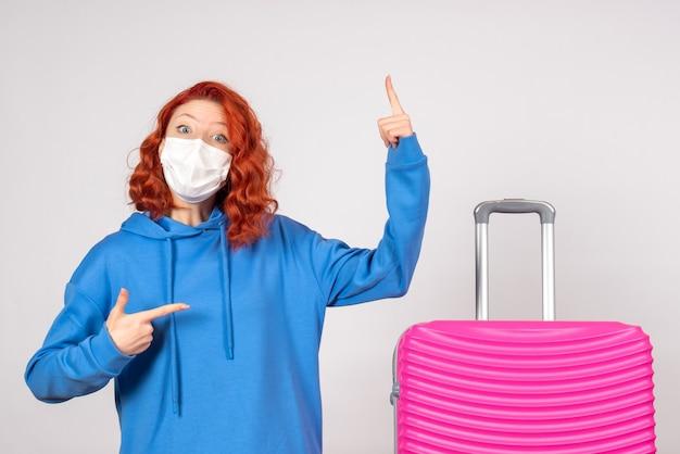 Vista frontal de uma jovem turista com bolsa rosa na máscara na parede branca