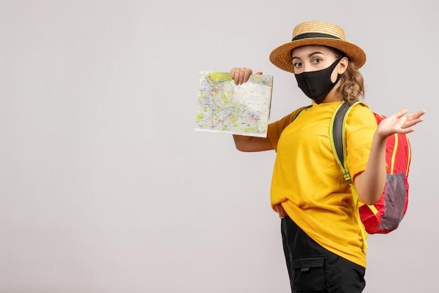 Vista frontal de uma jovem viajante com máscara preta segurando um mapa na parede branca