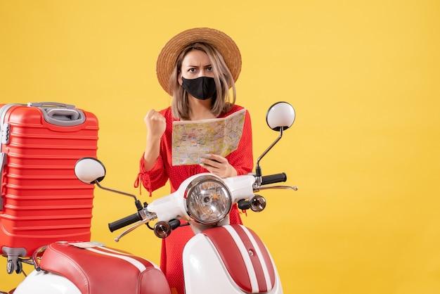 Vista frontal de uma jovem zangada com uma máscara preta segurando um mapa perto de uma motocicleta