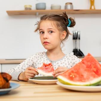 Vista frontal de uma linda garota comendo melancia