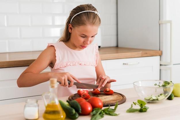 Vista frontal de uma linda garota cozinhando