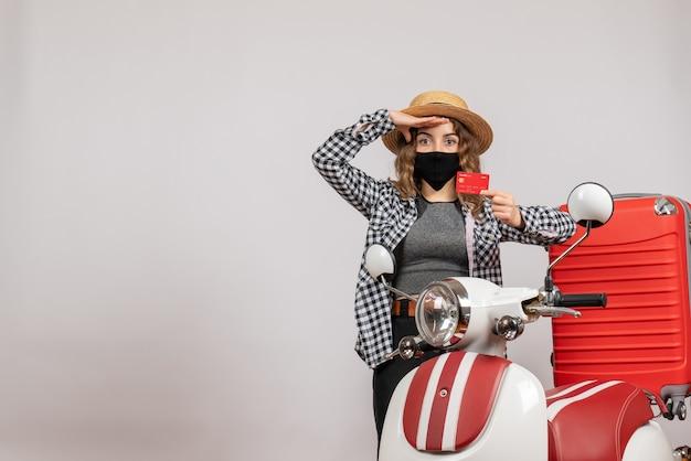 Vista frontal de uma linda garota jovem com máscara preta segurando o bilhete em pé perto de motocicleta vermelha na parede cinza isolada
