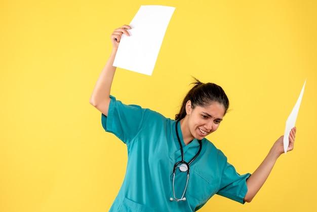 Vista frontal de uma linda médica segurando papéis com as duas mãos na parede amarela