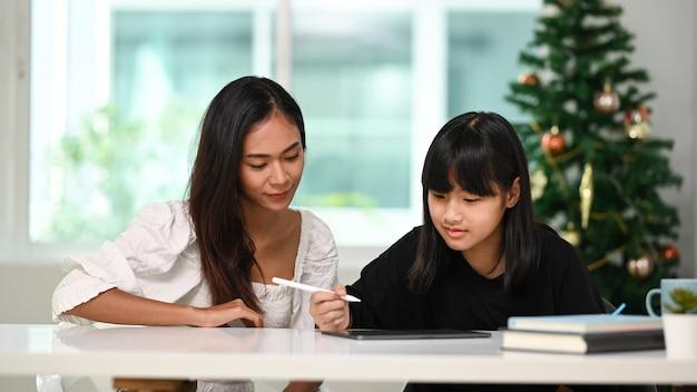 Vista frontal de uma linda mulher ajudando a filha a fazer o dever de casa online no tablet digital em casa.