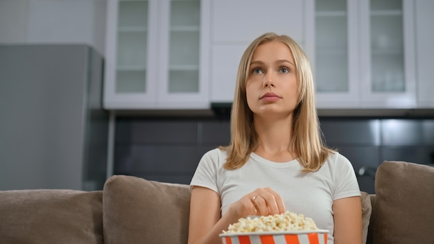 Vista frontal de uma linda mulher com admiração, assistindo tv e comendo pipoca.
