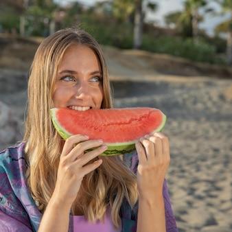 Vista frontal de uma linda mulher comendo melancia