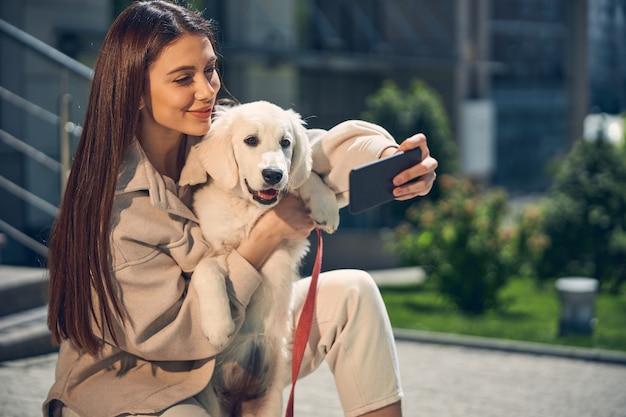 Vista frontal de uma linda mulher e seu cachorrinho posando em frente à câmera do smartphone