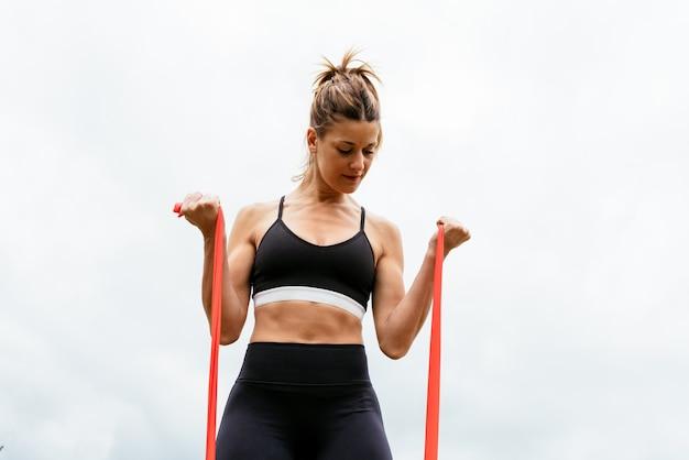 Vista frontal de uma linda mulher fazendo exercícios com um elástico em um fundo branco