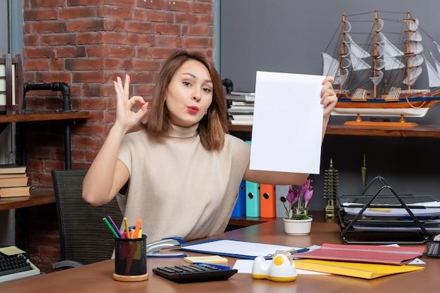 Vista frontal de uma linda mulher fazendo sinal de ok sentado na parede