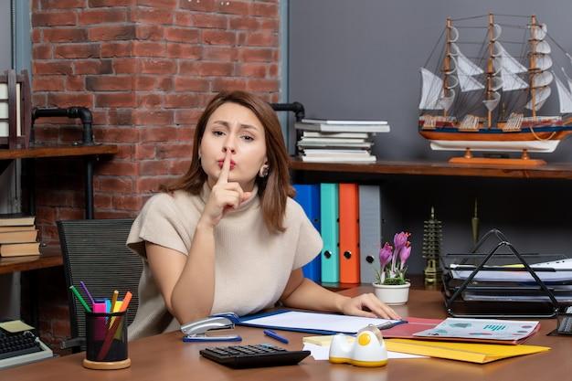 Vista frontal de uma linda mulher fazendo sinal de silêncio trabalhando no escritório