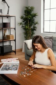 Vista frontal de uma linda mulher fazendo um quebra-cabeça