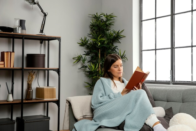 Vista frontal de uma linda mulher lendo um livro