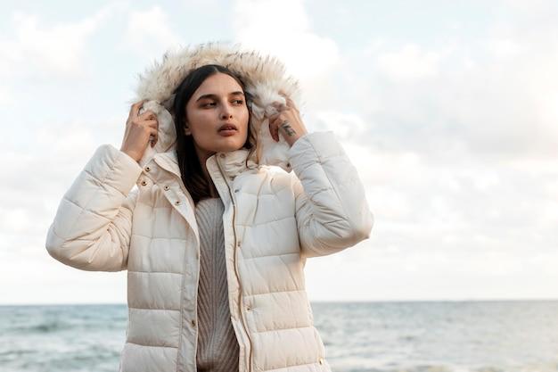 Vista frontal de uma linda mulher na praia com jaqueta de inverno