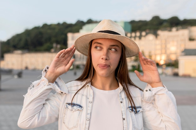 Vista frontal de uma linda mulher posando com chapéu enquanto viaja sozinha